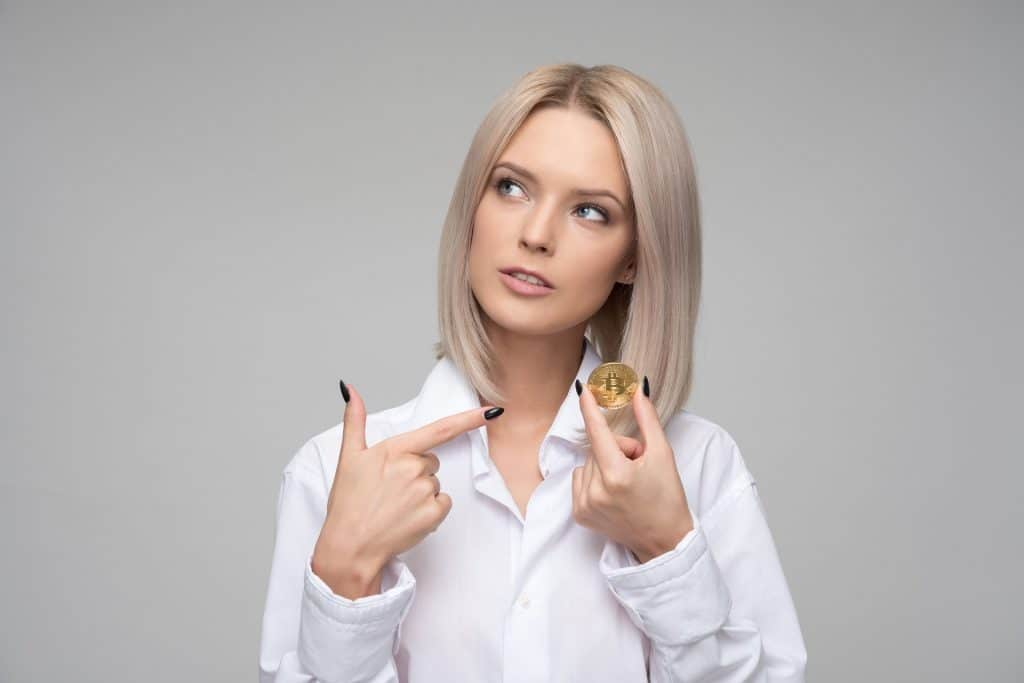A woman holding a cryptocurrency with a finger pointing at the coin.