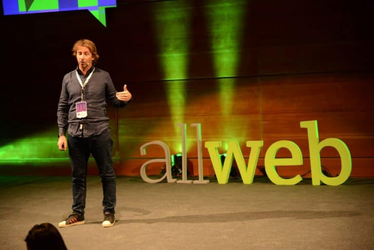 "Alessandro Angilella holding his conference with the text ""allweb"" in the background."