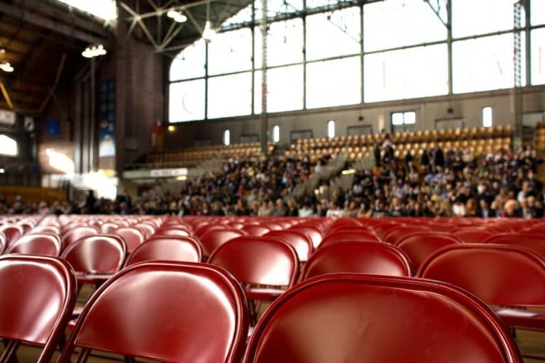 A presentation hall half empty, with the empty chairs in focus.