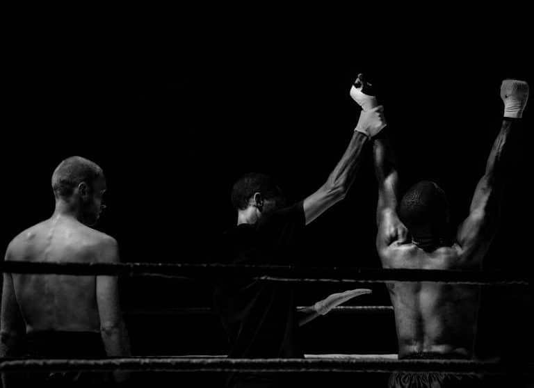 A boxing match after the finish, two fighters and a jugde, with the winner having the arms up in the air in a victory pose.